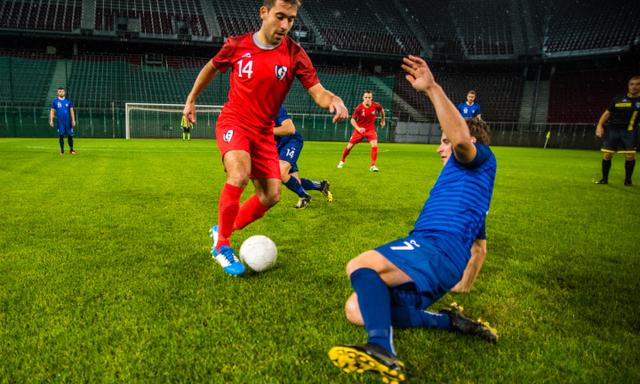 Male football players challenging for ball on field during match.