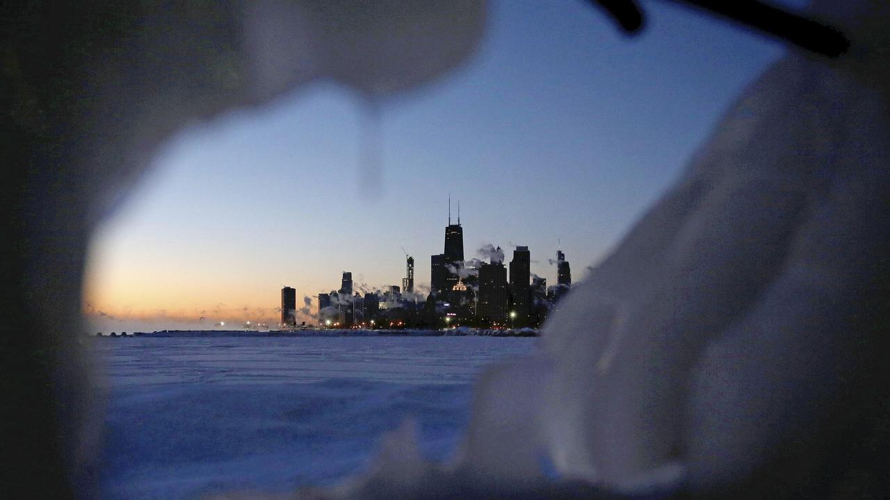 Ice forms along the shore of Lake Michigan before sunrise on Thursday in Chicago. Picture: Kiichiro Sato/AP