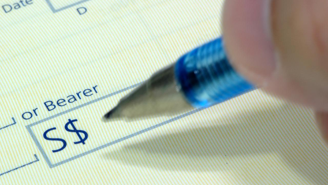 A person writing out a cheque. Picture: iStock