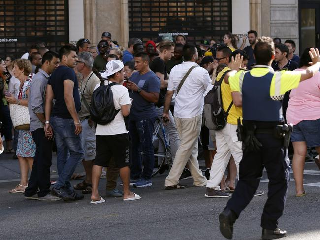 Policemen ask people to move back near a cordoned off area after a van ploughed into the crowd. Picture: AFP