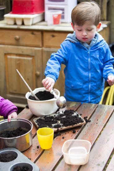 A vertical image of ta little boy outdoors using a bowl and kitchen utensils to make mud pies. The boy is wrapped up warm in a coat and are contently playing.