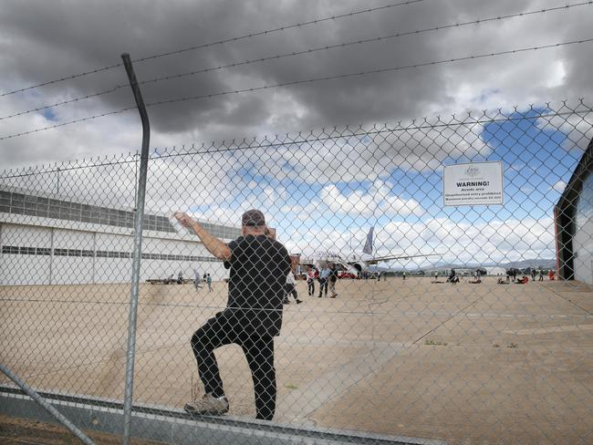 Waiting....Stranded passengers sit and wait on a military tarmac in Canberra. Picture: News Corp Australia