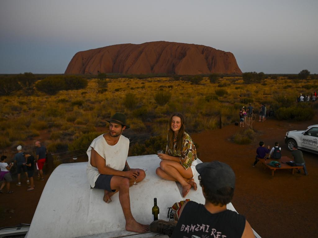 Sean Ruiper and Kristina Key observe Uluru from the top of their camper van during sunset at Uluru-Kata Tjuta National Park in the Northern Territory. Picture: AAP Image/Lukas Coch.