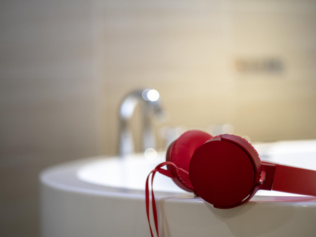 Headphones sit on the edge of a sink.