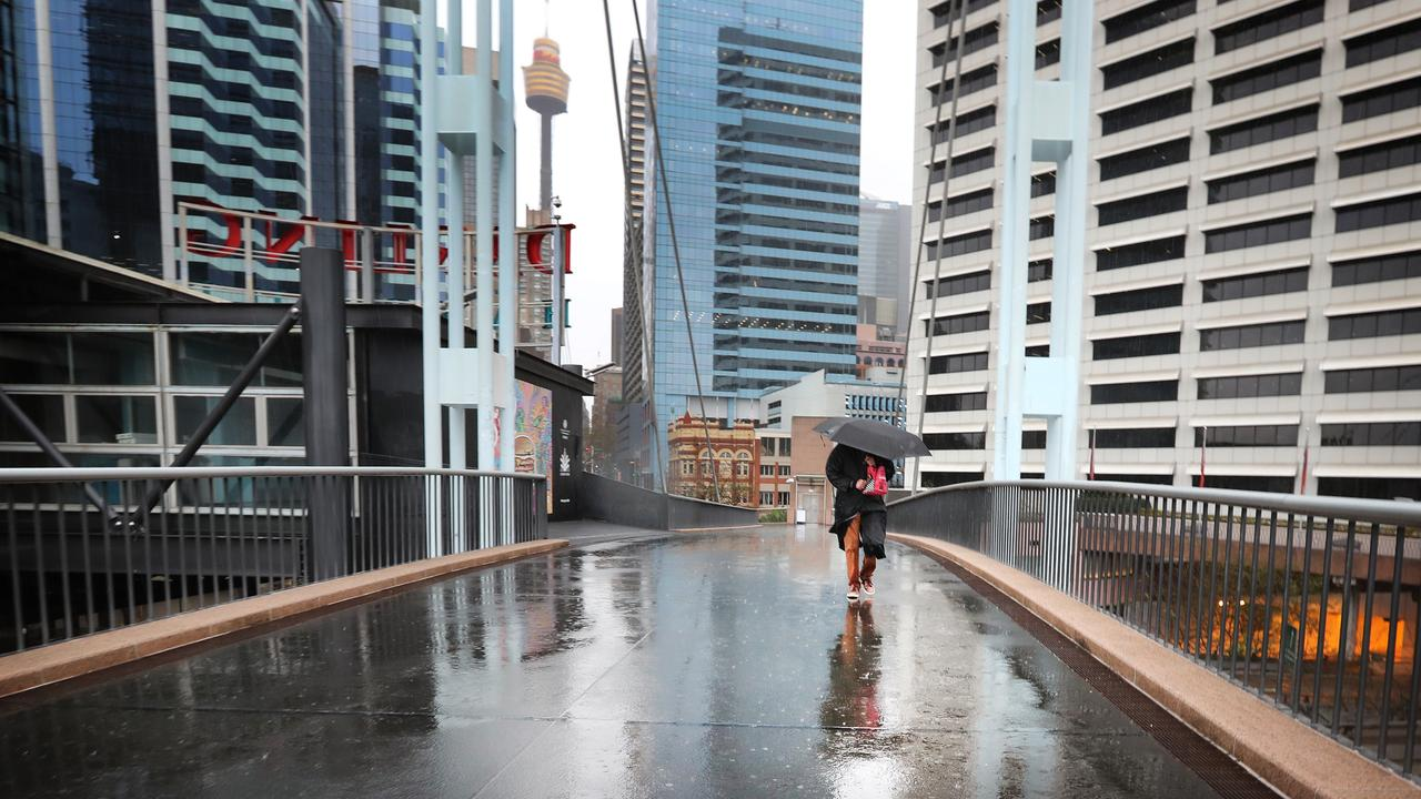 A pedestrian crosses a city footbridge during a rainy day in locked-down Sydney. New ABS statistics reveal the dire situation for payroll jobs in the city, with nearly 10 per cent of payrolled employees losing their job over the first five weeks of lockdown.