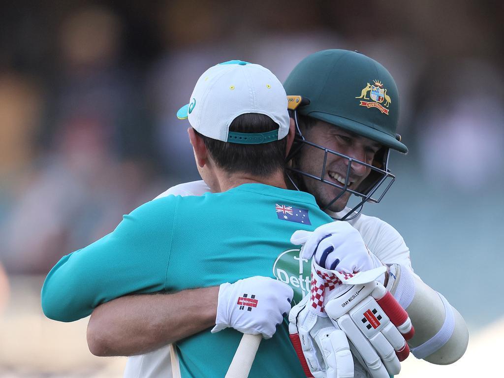 Joe Burns and Justin Langer share a hug.