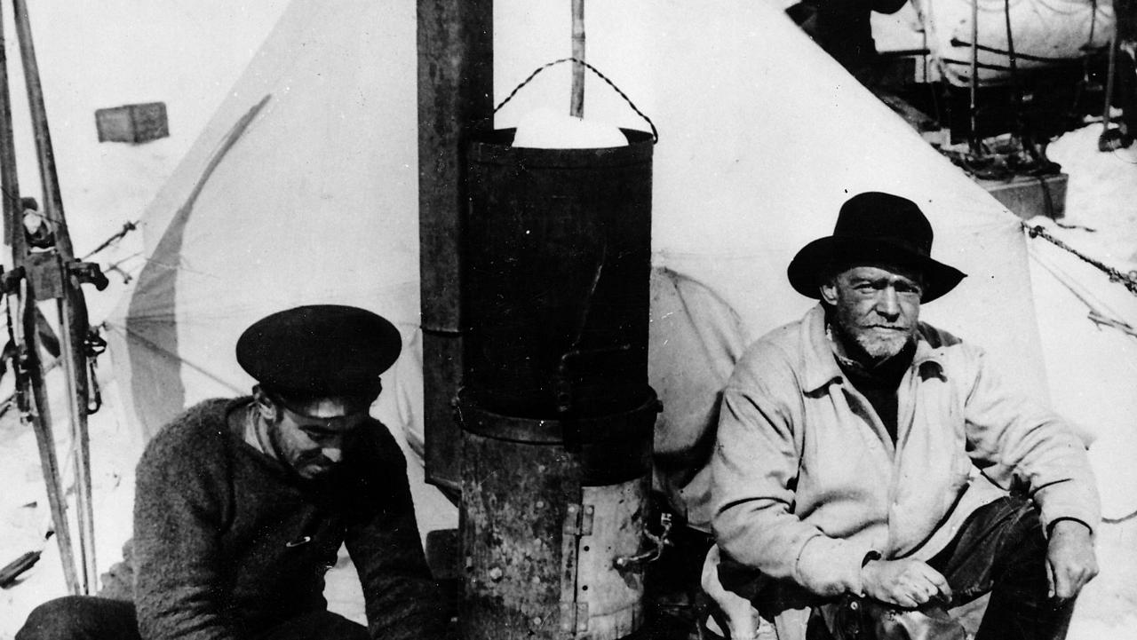 Historical antarctic images from Mercury files: Shackleton 1914 expedition. Frank Hurley, left, and Sir Ernest Shackleton in front of the tent in which they lived durng their six months adrift on an ice floe. Hurley is cutting up seal blubber to cook on the stove he made from fragments of the wrecked ship the Endurance