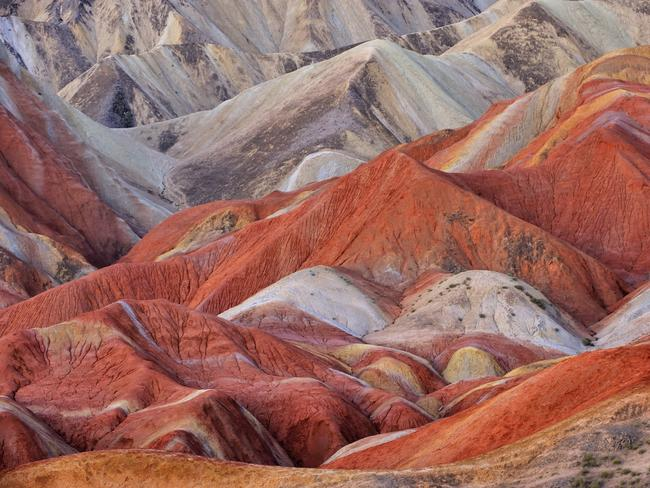 ZHANGYE DANXIA GEOLOGICAL PARK The colours are formed both by erosion and the precipitation of groundwater, which moves between the grains and deposits trace minerals, such as iron oxide, as it goes. Red, rust-like sandstone is the primary canvas and it incorporates a range of hues, including purple, yellow, green and grey.