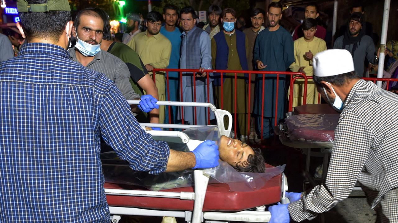 Volunteers and medical staff bring an injured man on a stretcher to a hospital for treatment after two powerful explosions outside the airport in Kabul. Picture: Wakil Kohsar/AFP
