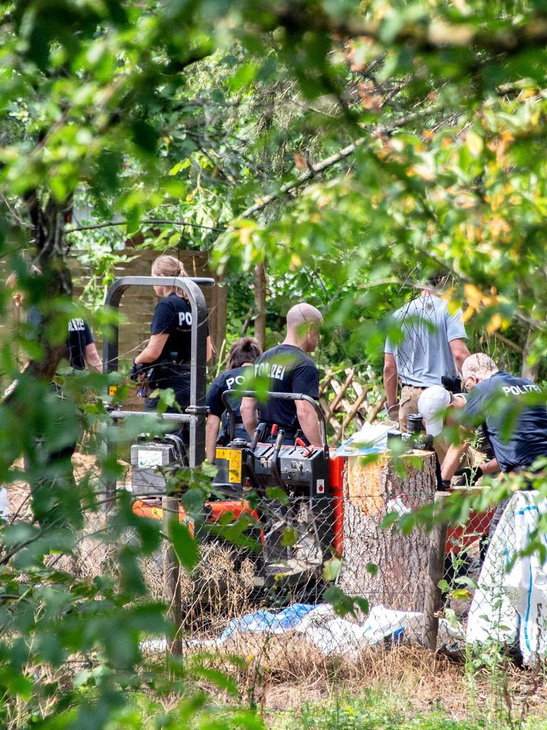Police officers search a garden for anything in connection with Madeleine McCann. Picture: Hauke-Christian Dittrich / AFP