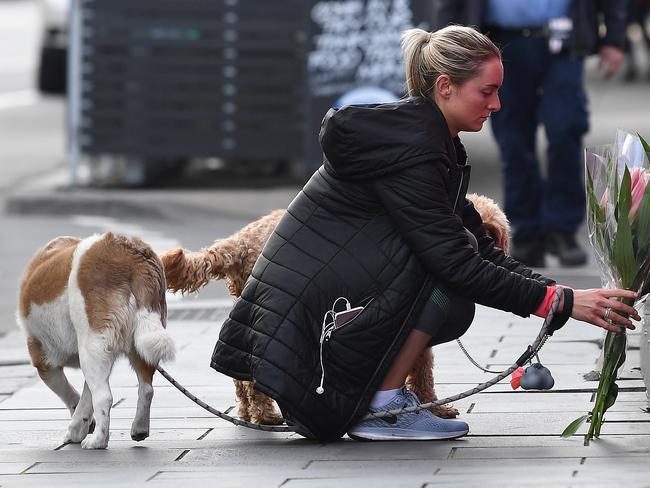 A woman places a floral tribute at Chapel Street, South Yarra where a 27-year-old Dutch female cyclist was hit by a stolen car. Picture: Julian Smith/AAP