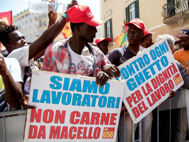 Migrant workers hold banners reading 'we are workers not butcher meat' and 'against every ghetto for the dignity of work'. Picture: Roberto D'Agonstino/AFP