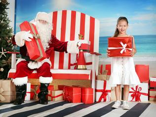 Pictured in Cronulla is a socially distanced Santa with local girl Edie Docherty (7). Children have had their minds eased knowing that Santa will go about his Christmas 2020 duties in a socially distanced fashion. Picture: Richard Dobson
