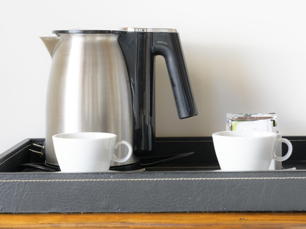 Electric coffee pot main by stainless with two white cup of coffee placing on a wooden small table besides bed