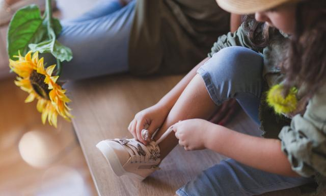32 years old woman is learning her daughter how to tie shoelaces
