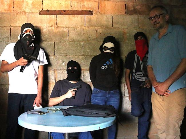 """Eric Campbell poses with gangsters in Caracas. """"They showed off all their guns to us,"""" he said. Picture: Courtesy of the ABC"""
