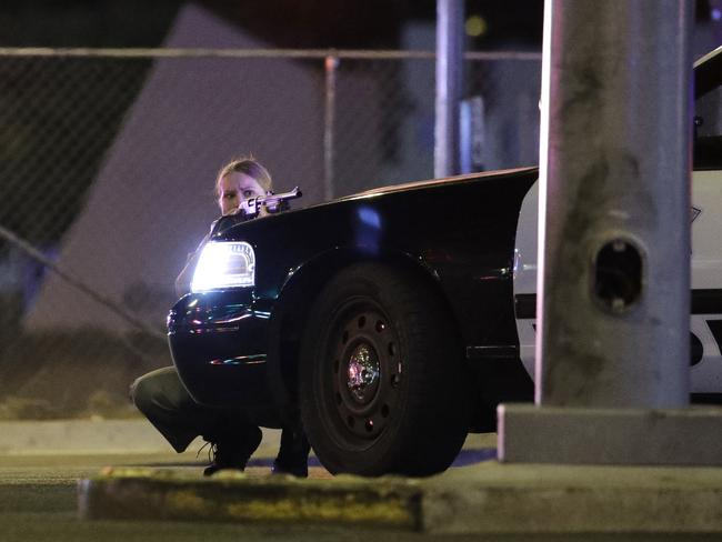 A police officer takes cover behind a police vehicle during a shooting near the Mandalay Bay resort and casino on the Las Vegas Strip. Picture: AP /John Locher