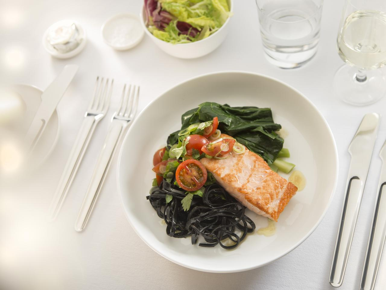 Grilled salmon with chilli, garlic, cherry tomatoes and squid ink noodles. Qantas first class menu. Picture: Qantas