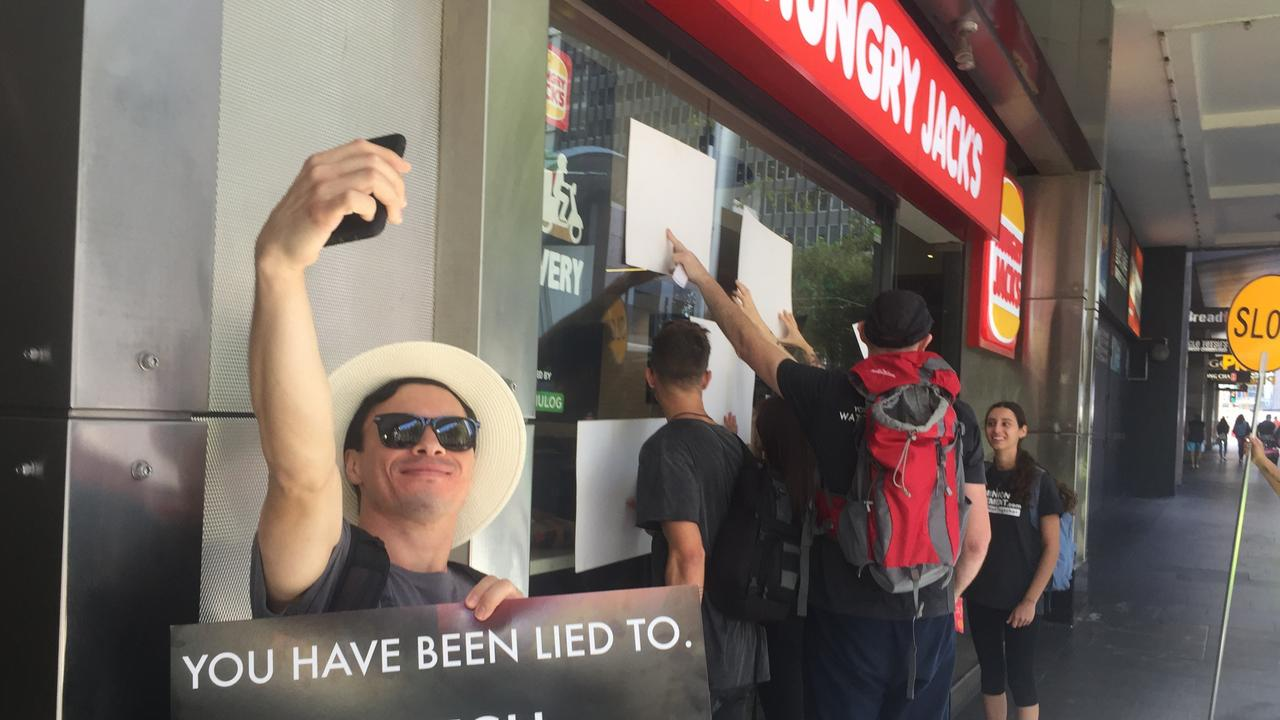 Vegan protesters slam their signs onto a Sydney CBD Hungry Jacks outlet and take selfies to document their rally. Picture: Derrick Krusche