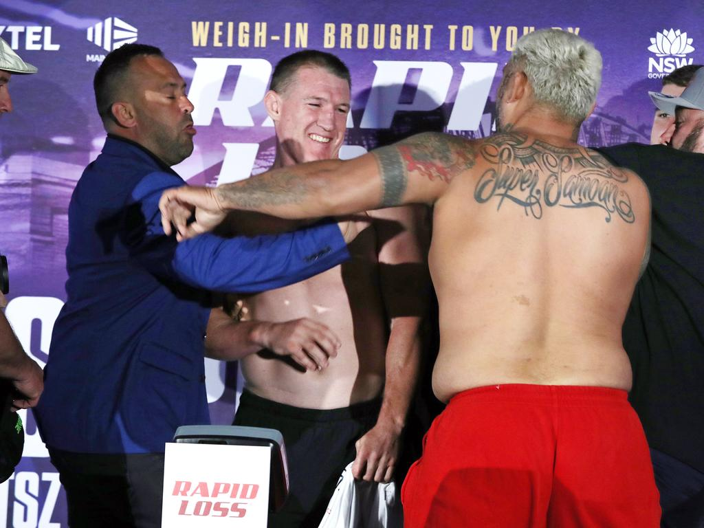 Paul Gallen smiles as Mark Hunt throws a punch towards him.