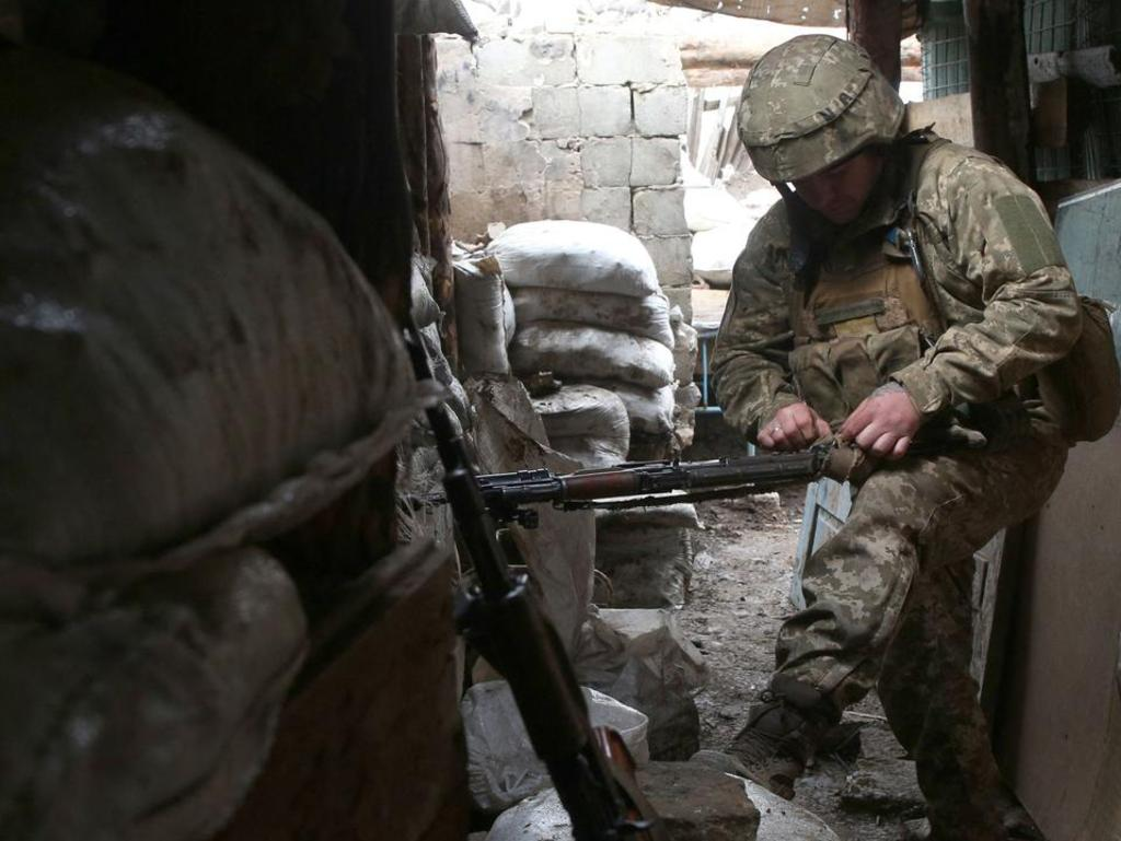 A Ukrainian serviceman cleans his machine gun at a position on the frontline with Russia-backed separatists near Gorlivka, Donetsk region.
