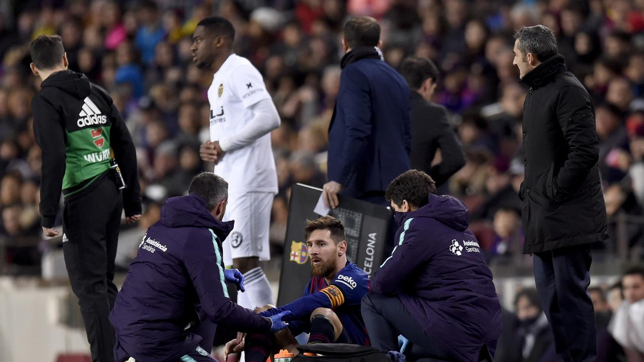 Lionel Messi of Barcelona receives medical treatment