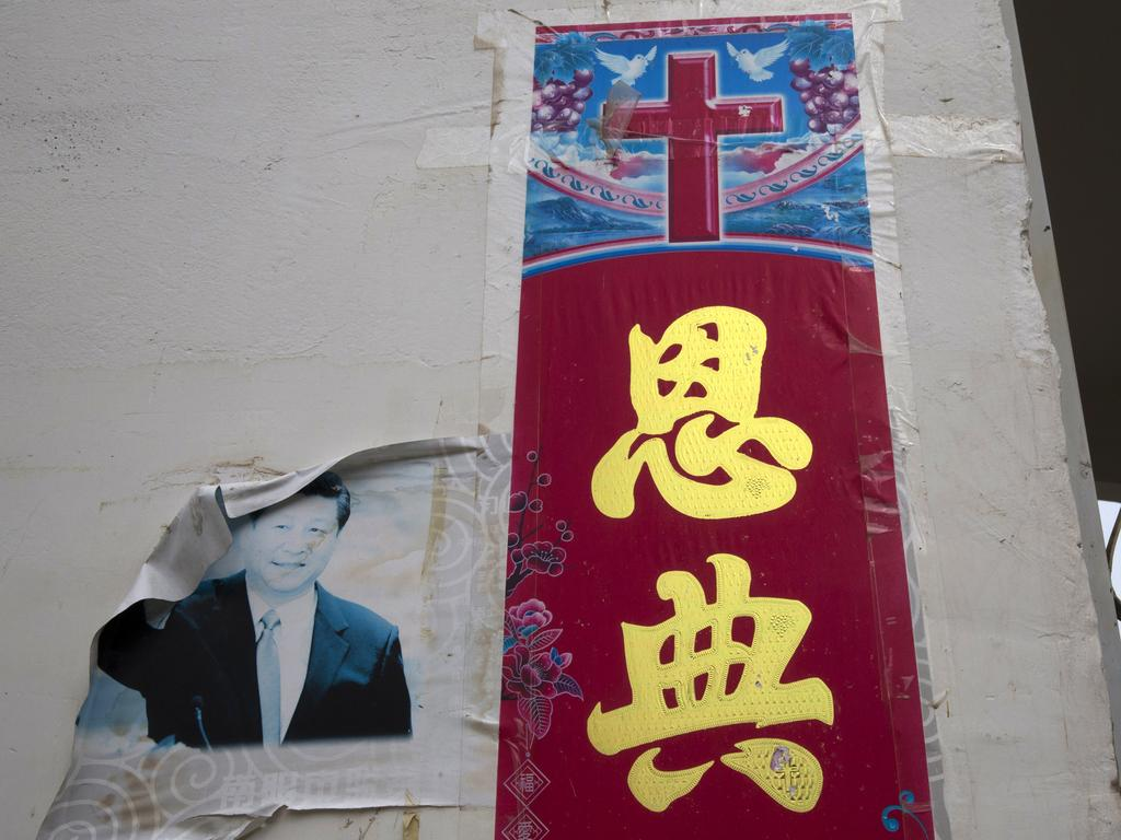 """A faded photo of Chinese President Xi Jinping is seen glued on a wall near a Christian poster with the word """"Grace"""" outside a house church near Nanyang in central China's Henan province. Picture: AP"""