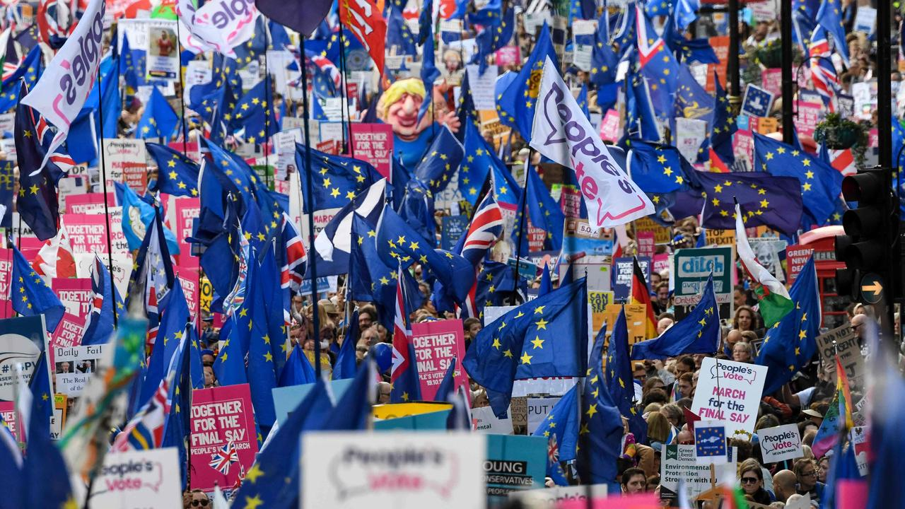 """Demonstrators hold placards and EU and Union flags as they take part in a march by the People's Vote organisation in central London. Up to one million marched to parliament calling for a """"People's Vote"""", with an option to reverse Brexit. Photo:by Niklas Hallen/AFP"""