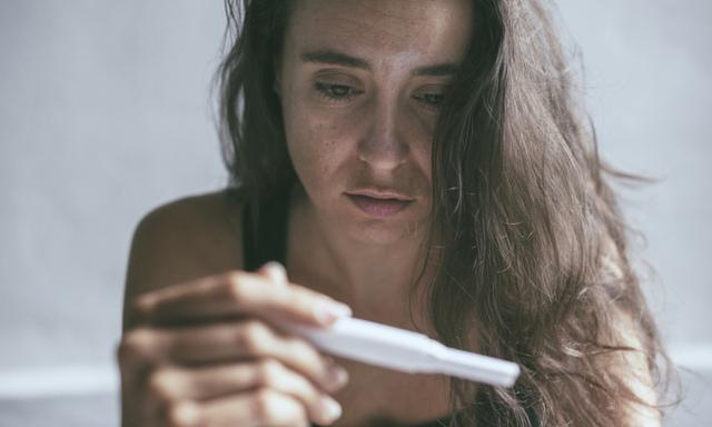 Woman holding pregnancy test with depressed worried face expression
