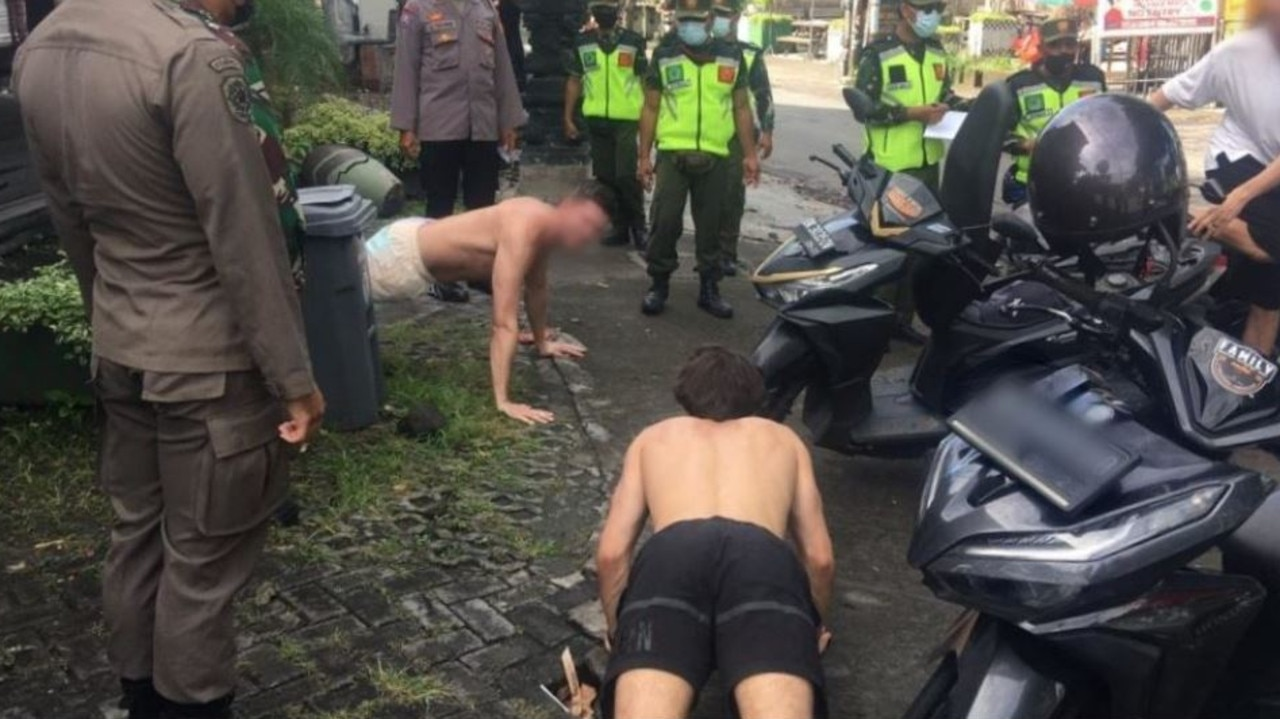 Foreigners in Bali are forced to do push-ups after being caught flouting COVID-19 mask rules. Picture: Satpol PP Badung