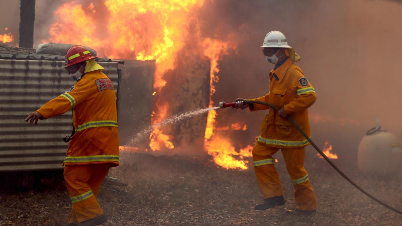 Firefighters hold back a fire threatening a house on The Buckets Way at Tinonee near Taree on the NSW mid north coast. Picture Nathan Edwards.