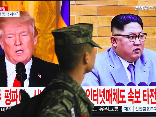 A South Korean soldier walks past a television screen showing pictures of US President Donald Trump and North Korean leader Kim Jong-un after the pair agreed to a historic first meeting. Picture: AFP Photo/Jung Yeon-je