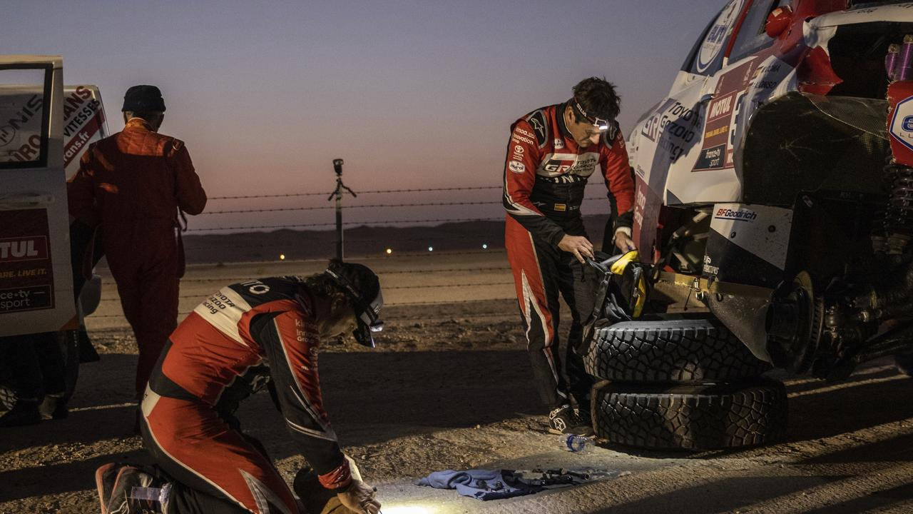 Fernando Alonso and co-driver Marc Coma repair their Toyota after rolling over during Stage 10.