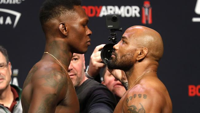 UFC middleweight champion Israel Adesanya, front left, of Nigeria, and challenger Yoel Romero, right, of Cuba, face off during a ceremonial weigh-in for UFC 248 at T-Mobile Arena in Las Vegas, Friday, March 6, 2020. UFC president Dana White keeps the fighters separated. Adesanya will defend his title against Romero at the arena on Saturday, March 7. (Steve Marcus/Las Vegas Sun via AP)