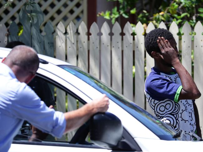 An unidentified man shields his face from cameras outside the house where the children were killed.