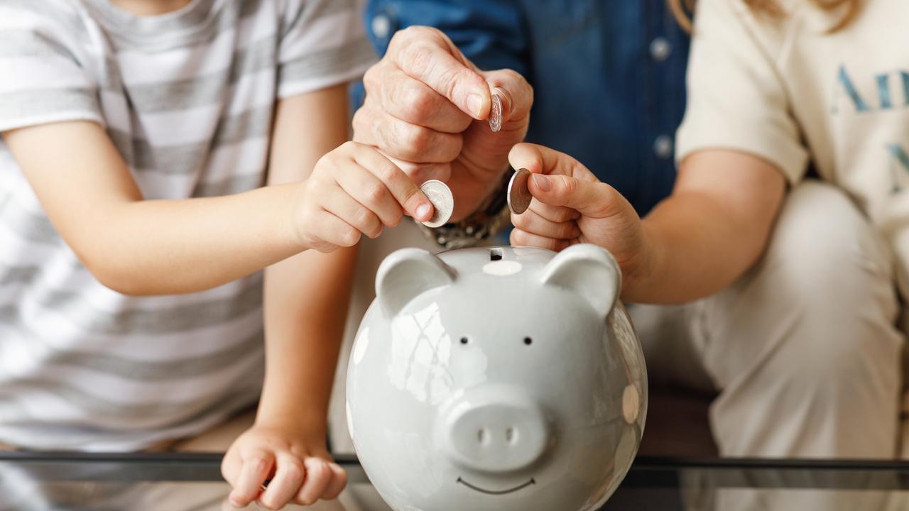 Crop grandfather and grandchildren saving money