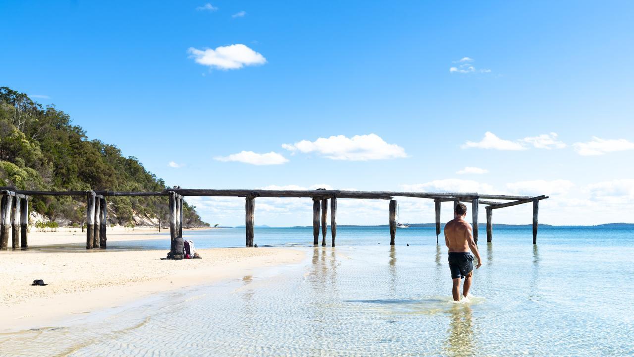 A man walking through the water at McKenzie Jetty at K'gari.