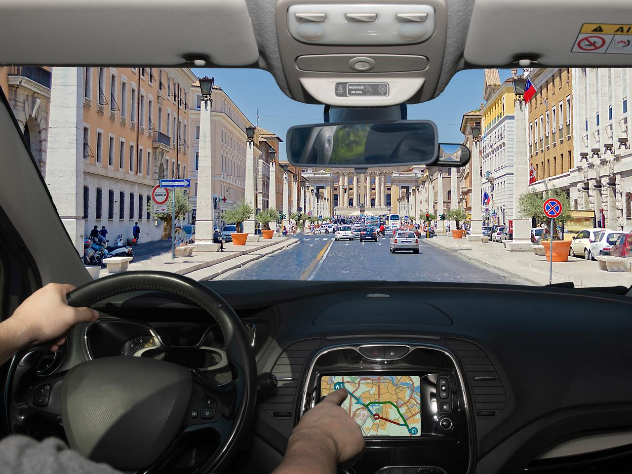 Driving a car while using the touch screen of a GPS navigation system on the scenic Via della Conciliazione leading to St. Peter's Church, Rome, Italy