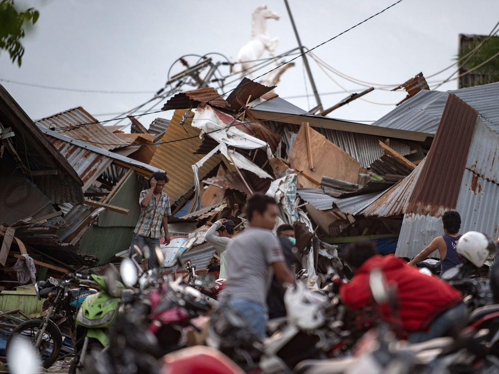Residents look for their belongings amid the debris of destroyed houses in Palu in Central Sulawesi. Picture: AFP