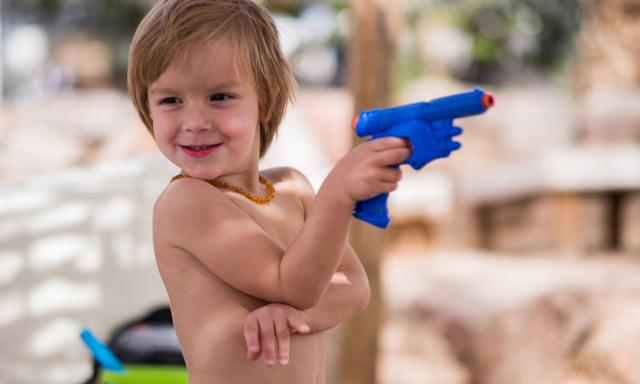 Little boy is playing with water gun