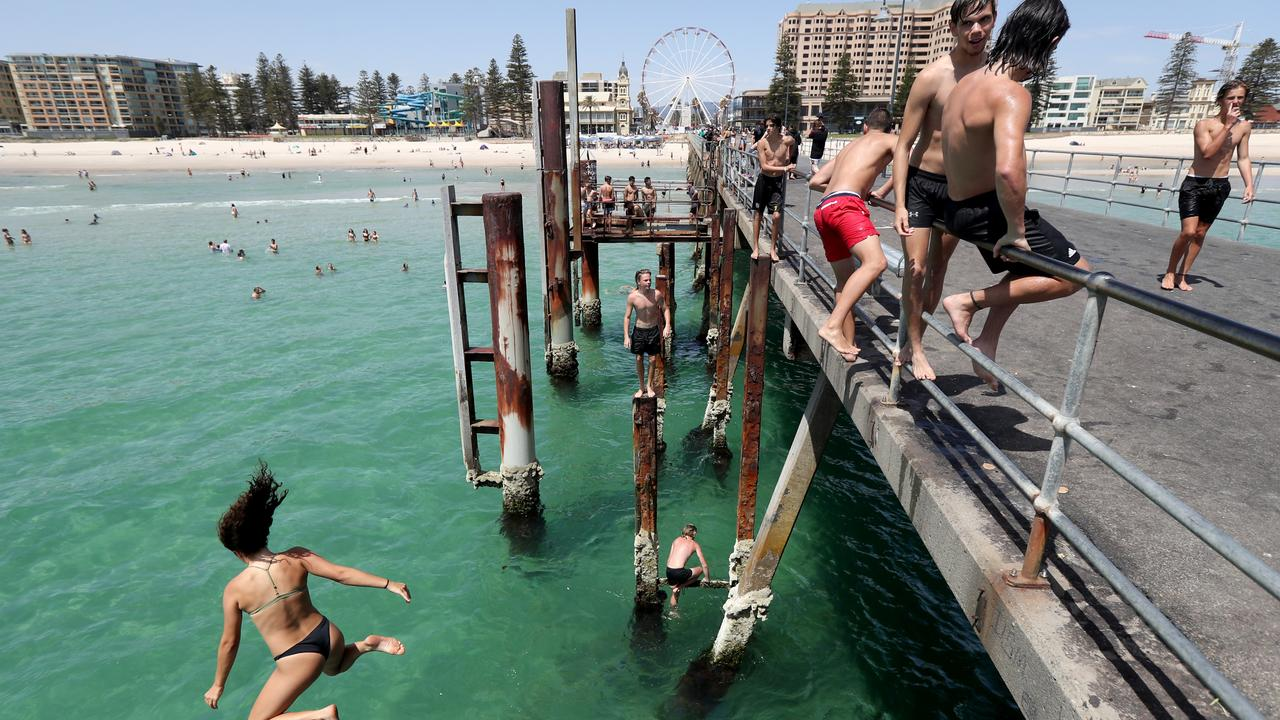 Teens jump of the jetty at Glenelg beach in Adelaide on Tuesday. Picture: Kelly Barnes/AAP