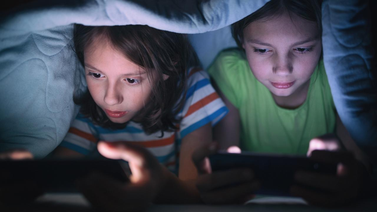 Boy and girl playing games on mobile phone in their bed
