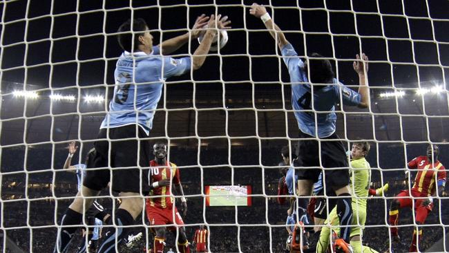 Uruguay's Luis Suarez, left, stops the ball with his hands during the 2010 World Cup quarter-final