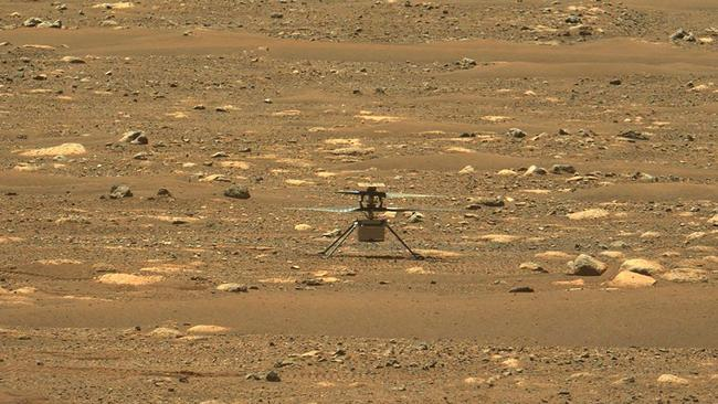 "This NASA photo was taken after the first flight of NASA's Ingenuity Mars Helicopter — and the first powered, controlled flight on another planet,  captured by Mastcam-Z, a pair of zoomable cameras aboard NASA's Perseverance Mars rover, on April 19, 2021. - Flying in a controlled manner on Mars is far more difficult than flying on Earth. Mars has significant gravity (about one-third that of Earth's), but its atmosphere is just 1 percent as dense as Earth's at the surface. Stitched together from multiple images, the mosaic is not white balanced; instead, it is displayed in a preliminary calibrated version of a natural color composite, approximately simulating the colors of the scene that we would see if we were there viewing it ourselves. (Photo by Handout / NASA/JPL-Caltech/MSSS/ASU / AFP) / RESTRICTED TO EDITORIAL USE - MANDATORY CREDIT ""AFP PHOTO / NASA/JPL-Caltech/MSSS/ASU/HANDOUT"" - NO MARKETING - NO ADVERTISING CAMPAIGNS - DISTRIBUTED AS A SERVICE TO CLIENTS"