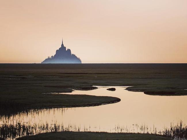 "MONT ST MICHEL, FRANCE ""When I took this picture, I was surrounded by sheep! I wanted to take a different picture, to show the Mont's silhouette in a unique way. The wide-open spaces dominate the landscape and one can guess the silhouette and the mist!"" – @pascalbiomez"