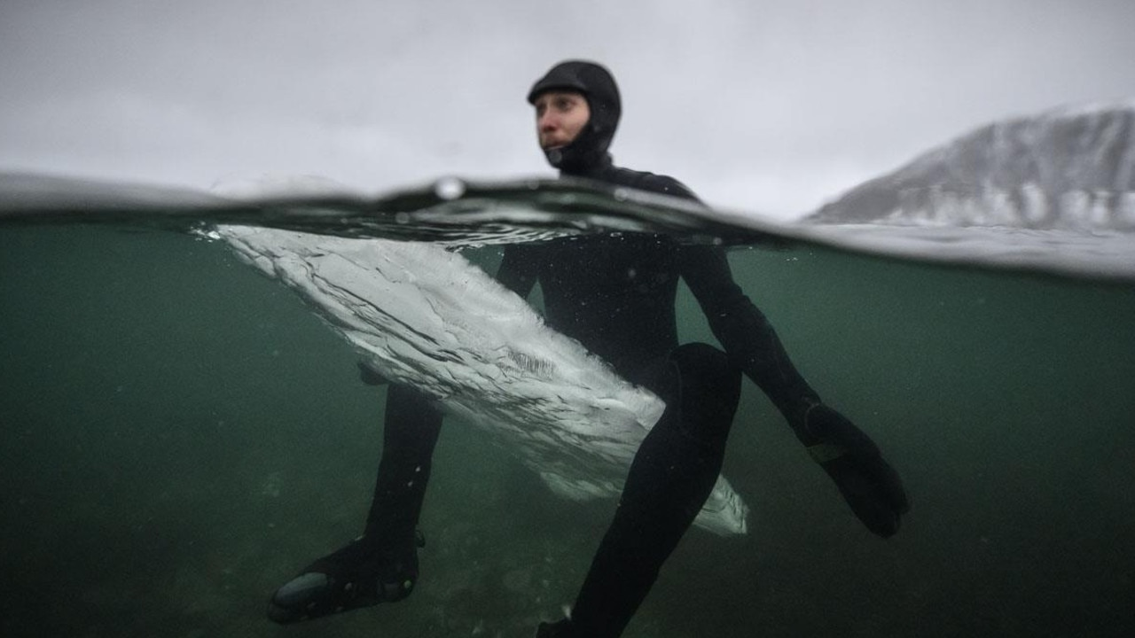 Swedish surfer Pontus Hallin waits for waves as he sits on his melting ice surfboard at the Delp surfing spot, near Straumnes, in the Lofoten Islands. Picture: AFP/Olivier Morin