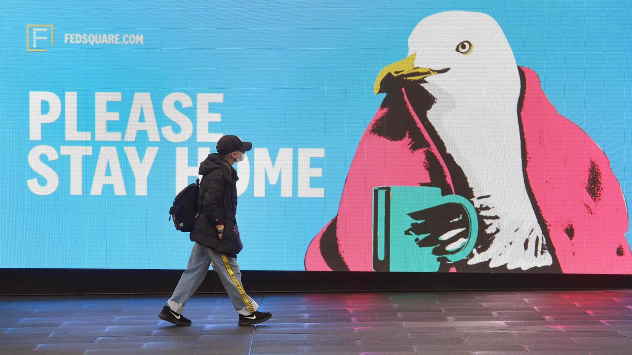 A woman walks past a sign urging people to stay home in Melbourne on August 14, 2020 as the city battles an outbreak of the COVID-19 coronavirus. Picture: AFP