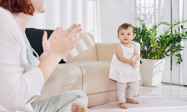 Mother applauding to her dancing little baby girl when they are staying home due to pandemic