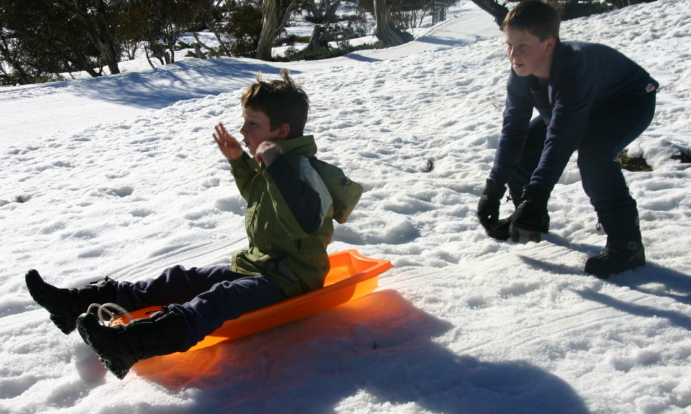 L to R:young autistic boy( 8 years) on toboggan and young boy(11 years) playing and enjoying the snow at Perisher, Snowy Mountains, NSW, Australia on 9 September 2014.