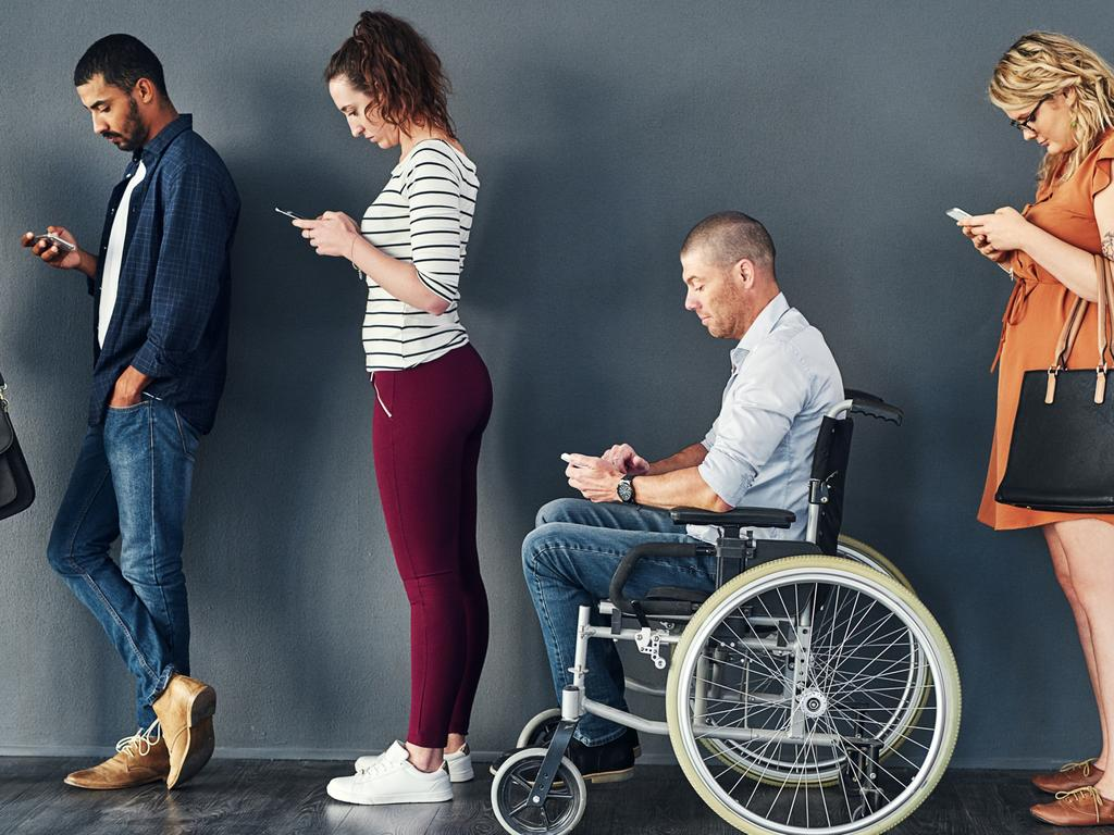 CAREERS: Studio shot of a man in a wheelchair waiting in line against a grey background